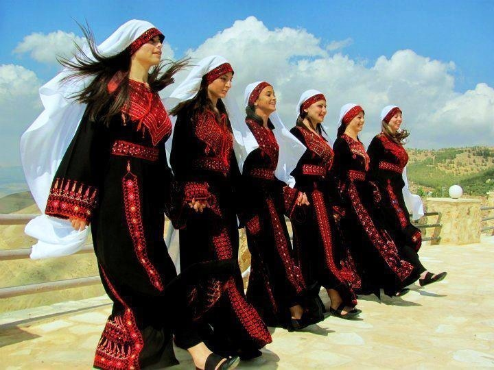 Young women in Palestinian Thobes doing the traditional dance - Dabka